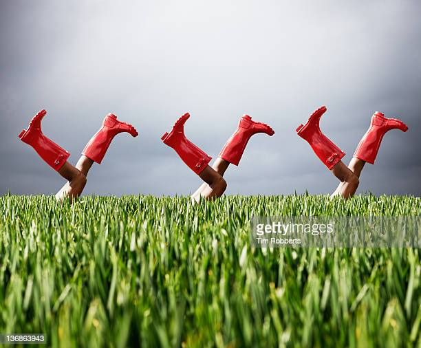 row of legs in the air wearing red boots. - 赤のブーツ ストックフォトと画像
