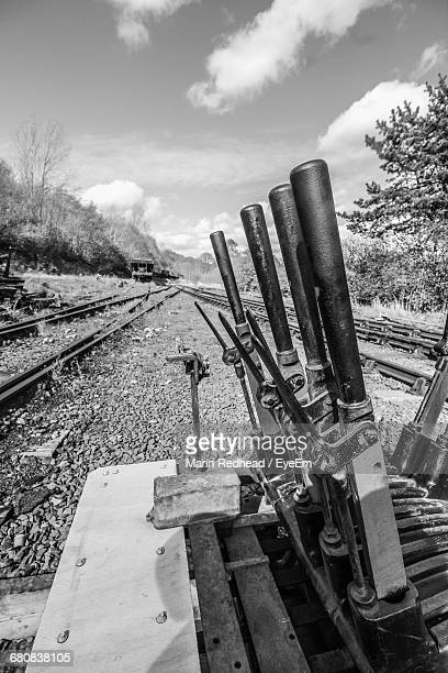 Row Of Levers By Railroad Tracks Against Sky