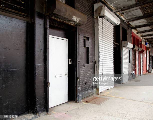row of loading bay doors - roller shutter stock pictures, royalty-free photos & images