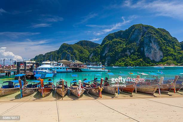 row of longtail boats at phi phi island - phuket province stock pictures, royalty-free photos & images