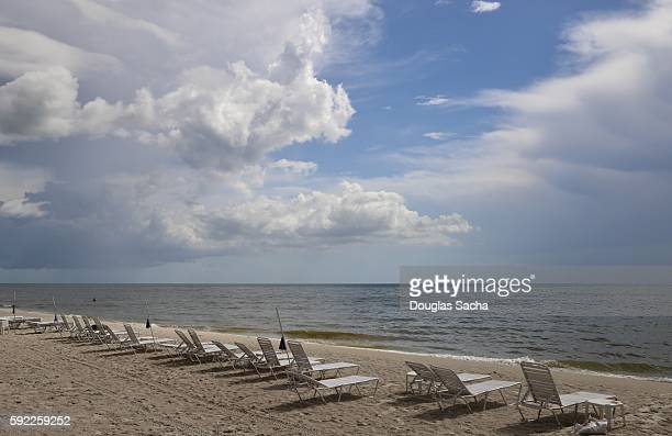 row of lounge chairs on a scenic ocean beach, delnor-wiggins pass state park, naples, florida, usa - state park stock pictures, royalty-free photos & images