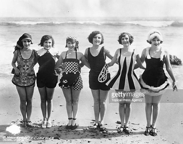 A row of Mack Sennett starlets showing off some unusual and original swimwear on the beach