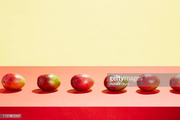 a row of mangos on a table top - mango fotografías e imágenes de stock