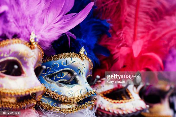 row of masks on display in venice - karneval stock-fotos und bilder