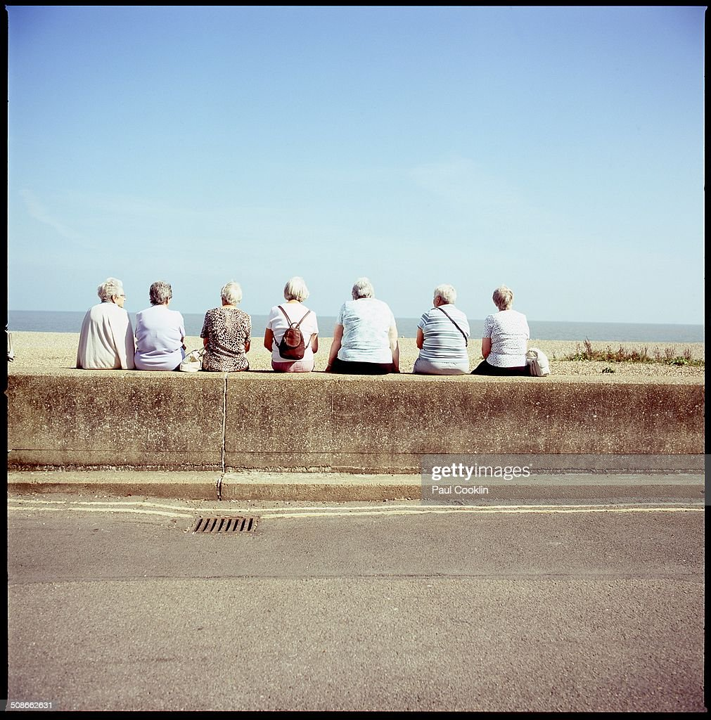 Row of Mature Women sitting on wall, Aldeburgh, Suffolk, February 2014