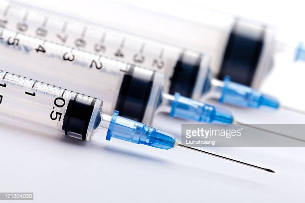 Row of medical syringes with blue lids