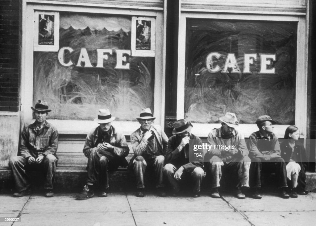 A row of men in overalls, and one girl, sit in front of an out-of-business cafe with soaped windows, during the Great Depression, United States.