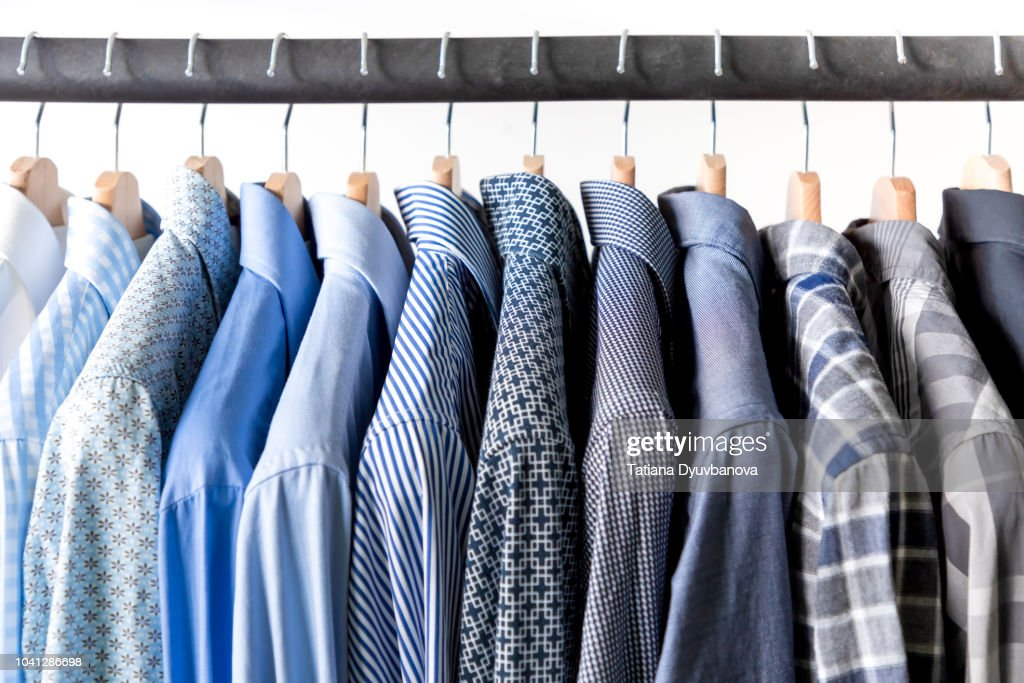 Row of men's shirts in blue colors on hanger : Stock Photo