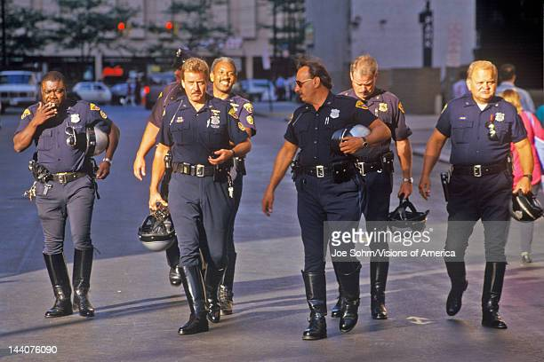 Row of motorcycle policeman casually walking