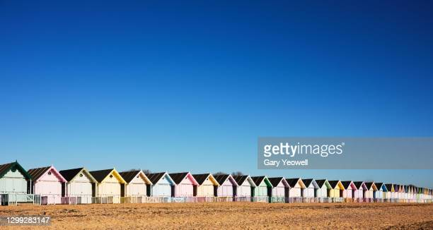 row of multi coloured beach huts - in a row stock pictures, royalty-free photos & images