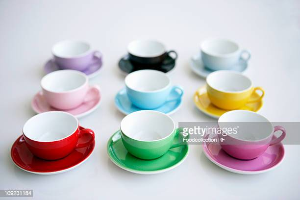 Row of multi coloured coffee cups and saucers