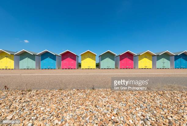 a row of multi-coloured beach huts along the promenade, eastbourne, east sussex - british culture stock pictures, royalty-free photos & images