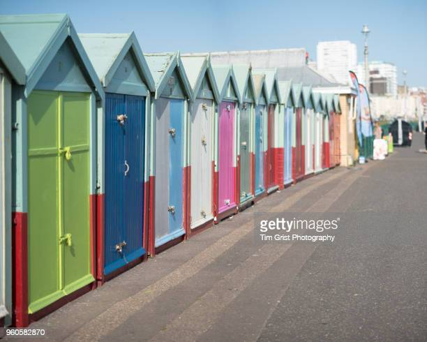 a row of multi-coloured beach huts on the promenade, brighton and hove - hove stock pictures, royalty-free photos & images