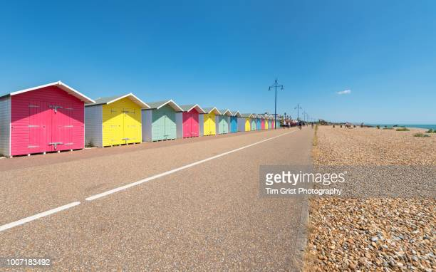 a row of multi-coloured beach huts - eastbourne stock pictures, royalty-free photos & images