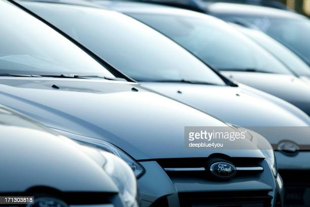 row of new ford focus vehicles at dealership - ford motor company stock pictures, royalty-free photos & images