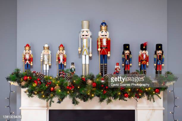 a row of nutcracker dolls on top of a fireplace at christmas - david soanes stock pictures, royalty-free photos & images