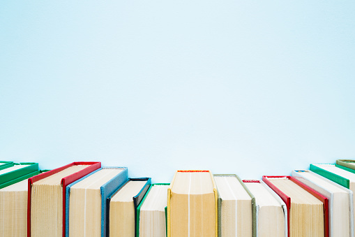 Row of old books with colorful covers on pastel blue background. Education concept. Mock up for different ideas. Empty place for text, quote or sayings. 1126130554
