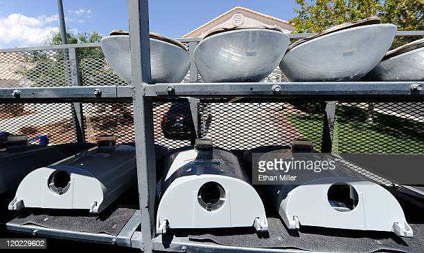 A row of old street lights are stacked on a truck above a row of new LED light fixtures as crews install the LEDs August 1 2011 in Las Vegas Nevada...