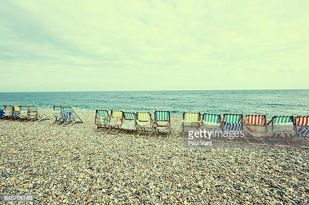 row of old style deckchairs on pebble beach