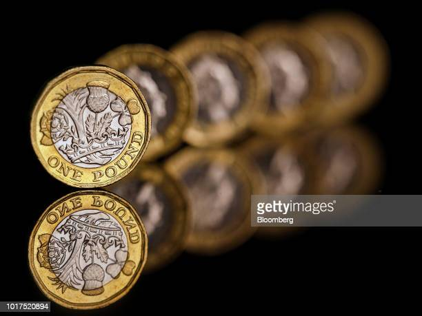 A row of one pound sterling coins stand in this arranged photograph in London UK on Wednesday Aug 15 2018 The pound's weakness is turning...