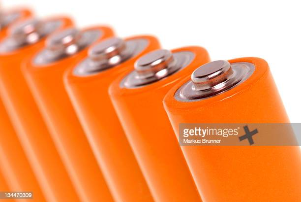row of orange batteries - plus key stock photos and pictures