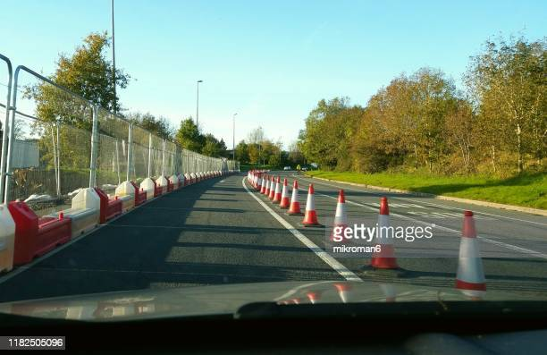 a row of orange construction barriers. road works - construction barrier stock pictures, royalty-free photos & images