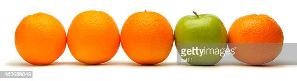 Row of oranges with a green apple.