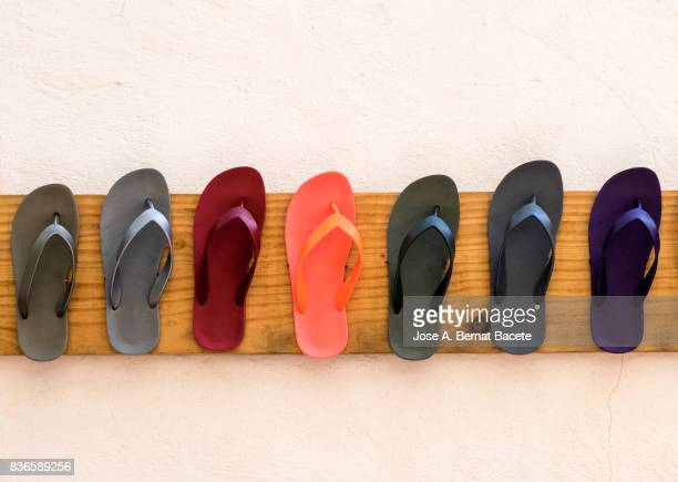 Row of  pair of flip flops of varied colors, hung on a wooden board in the street