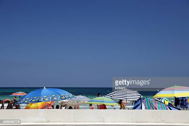 row of parasols and tourists on can picafort beach - skimpy bathing suits stock pictures, royalty-free photos & images