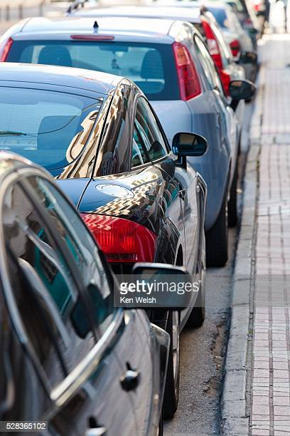 row of parked cars on a street - curb stock pictures, royalty-free photos & images