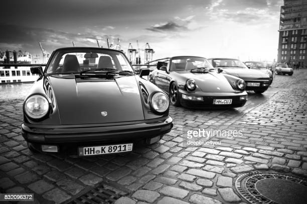 a row of parked porsche 911 vehicles during the event with magnus walker on the fish market hamburg - porsche carrera stock photos and pictures