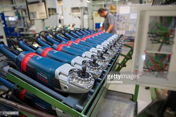 A row of partly assembled Bosch electric angle grinders wait on the assembly line at the professional power tools division of Robert Bosch GmbH in...