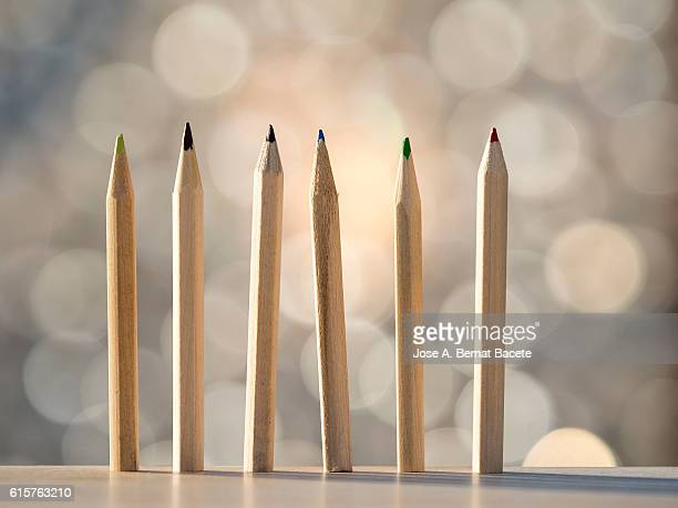 Row of pencils of wood of different colors on a multicolored natural bottom