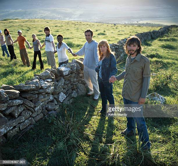 row of people holding hands over dry stone wall, portrait - stone wall imagens e fotografias de stock
