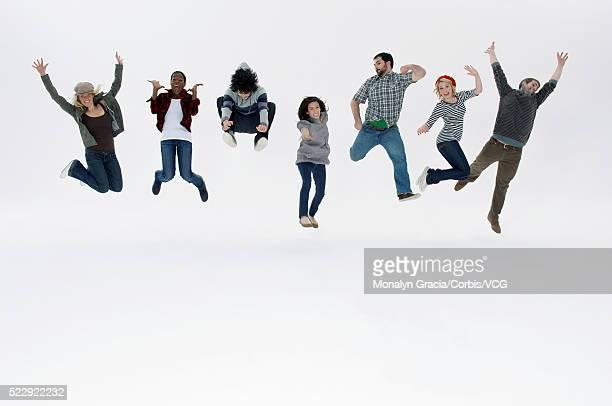 row of people jumping for joy - côte à côte photos et images de collection