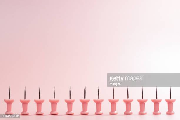 a row of pink thumbtack - stecknadel stock-fotos und bilder