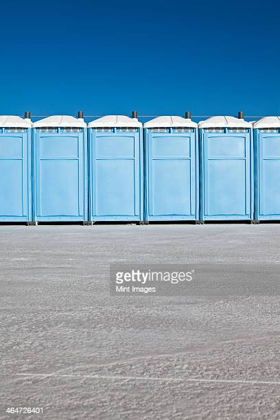 row of portable toilets on bonneville salt flats,during speed week - portable toilet stock photos and pictures