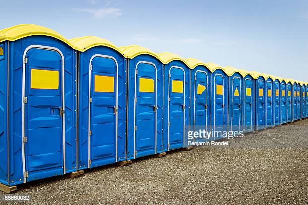 row of portable toilets - portable toilet stock photos and pictures