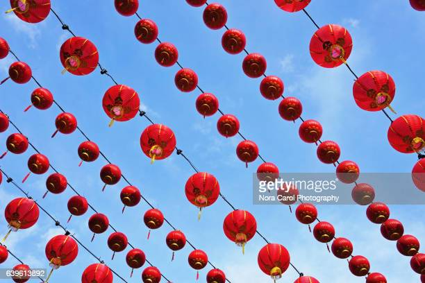 Row of red chinese lanterns against blue sky.