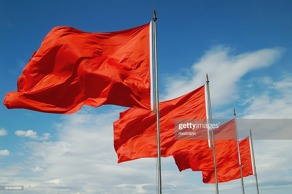 A row of red flags blowing in the wind : Stock Photo