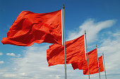A row of red flags blowing in the wind