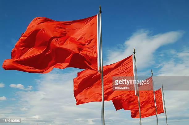 a row of red flags blowing in the wind - flag stock pictures, royalty-free photos & images