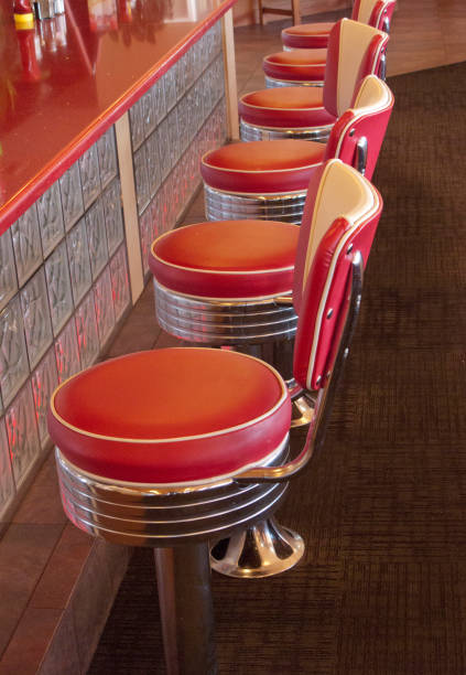 A row of red vinal soda fountain stools in a 1950's retro diner