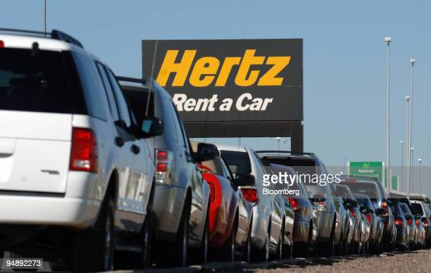 A row of rental cars are parked below a sign for Hertz Corp at Denver International Airport Monday September 12 2005 Ford Motor Co may sell Hertz...