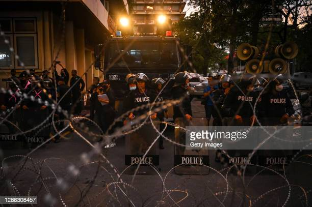 Row of riot police stand stationed in front of a water cannon behind barbed wire at the police headquarters on November 18, 2020 in Bangkok,...