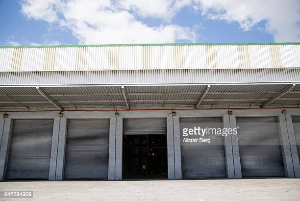 row of shutter doors at warehouse - industrial door stock pictures, royalty-free photos & images