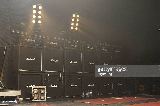 A row of six Marshall stack amplifiers and speaker cabs including two Wizard amplifier heads miked up and under stage lighting on stage at a music...