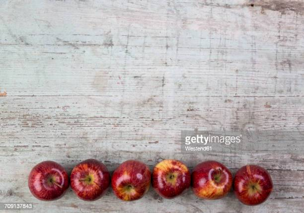 Row of six red apples