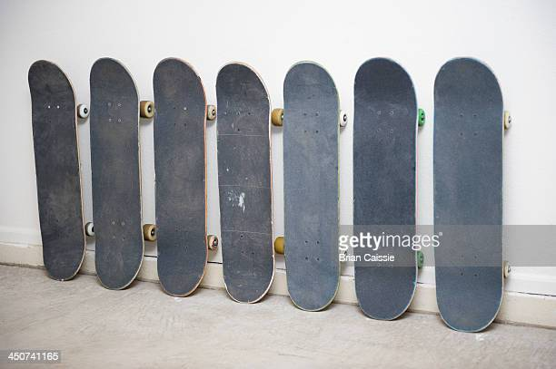 row of skateboards against wall, one has a painting of an american indian on it - medium group of objects stock pictures, royalty-free photos & images