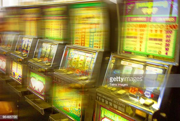 a row of slot machines - gambling addiction stock pictures, royalty-free photos & images